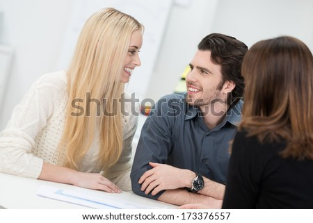 Happy couple looking at each other during in an interview in an office