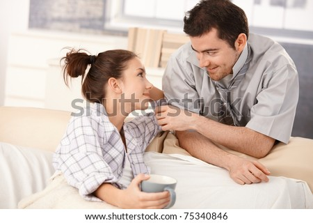 Happy couple looking at each other tenderly in the morning, woman laying in bed.? - stock photo