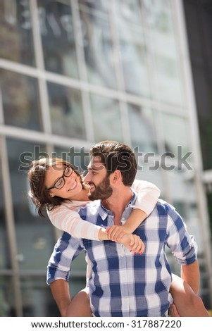 Happy couple looking at each other while enjoying piggyback ride in city - stock photo
