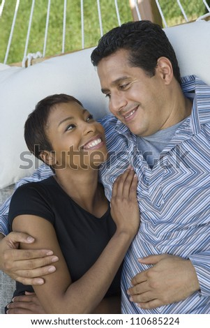 Happy couple looking at each other while lying on hammock - stock photo