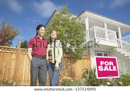 Happy couple looking at house for sale