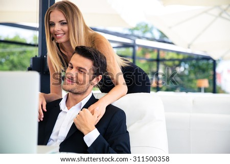 Happy couple looking at laptop in restaurant