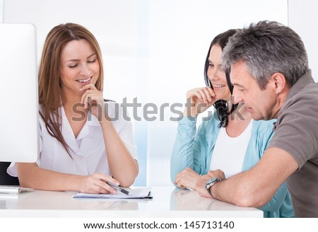 Happy Couple Looking At Results Held By Doctor - stock photo