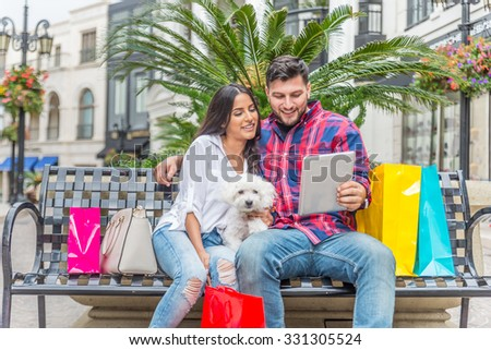 Happy couple looking at tablet while shopping - Boyfriend embracing his beautiful girlfriend with poodle in Beverly Hills - Rich persons having fun - stock photo