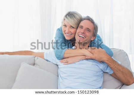 Happy couple looking at the camera at home on couch - stock photo