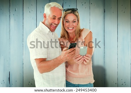 Happy couple looking at their smartphones against wooden planks - stock photo