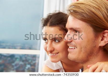 Happy couple looking away to the window with blue sky as background. ***