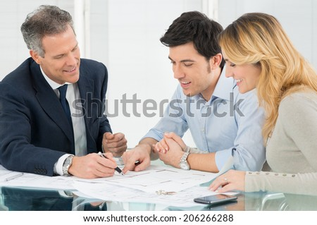 Happy Couple Looking Blueprint About New House  - stock photo