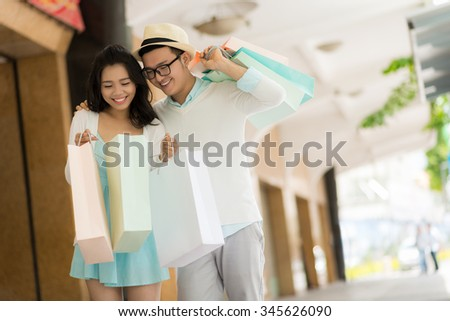 Happy couple looking into paper bag with purchases
