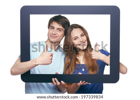 Happy couple looking through tablet frame and giving thumbs up - stock photo