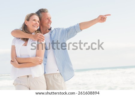 Happy couple looking to sea at the beach - stock photo