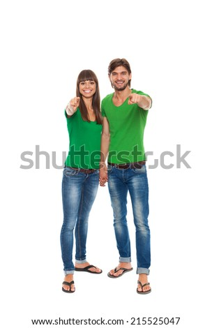 happy couple love excited smiling point finger at you gesture, beautiful young man and woman smile looking at camera, wear green t shirt isolated over white background