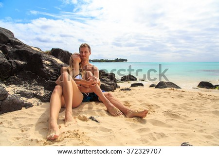 Happy couple lying at the beach by the rocks. Love is in the air. Romantic.