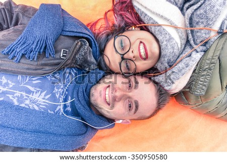 Happy couple lying down holding heads together looking up at the camera as posing for a selfie photo - Lovers hearing music together - Love togetherness youth concept - Soft cold filtered look - stock photo