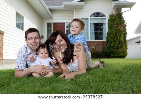 Happy couple lying down on grass with their adorable children