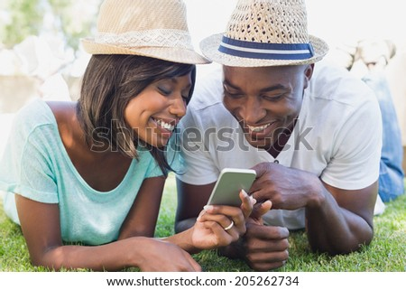Happy couple lying in garden together looking at smartphone on a sunny day