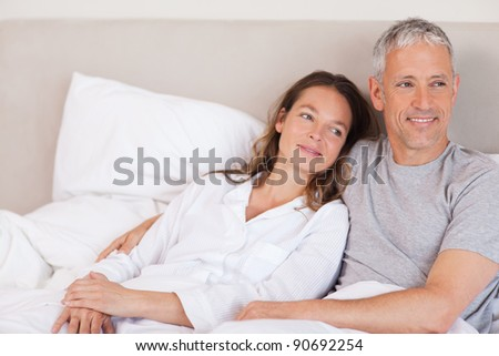 Happy couple lying on a bed looking away from the camera