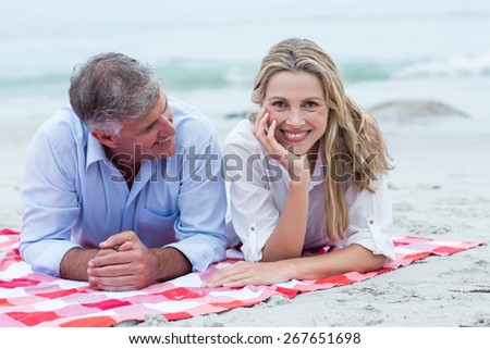 Happy couple lying on a blanket at the beach - stock photo