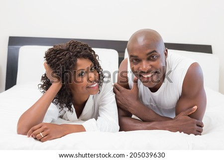 Happy couple lying on bed together at home in the bedroom - stock photo