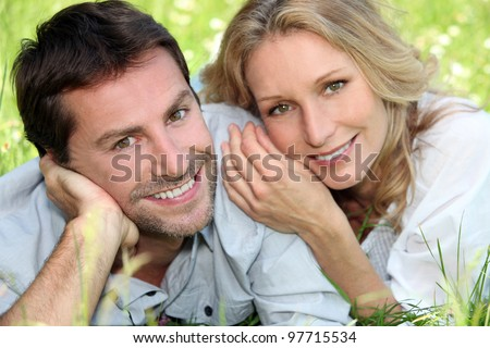 Happy couple lying on grass - stock photo