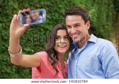 Happy couple making a photo of themselves - stock photo