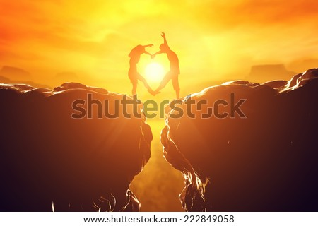 Happy couple making heart shape over precipice between two rocky mountains at sunset. Love unique concept. - stock photo
