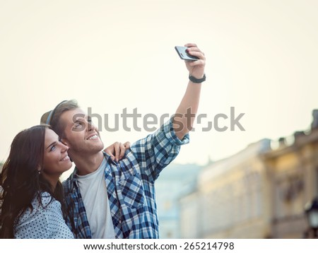 Happy couple making selfie outdoors - stock photo