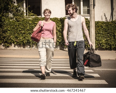 Happy couple man and woman with sport gym bags crossing pedestrian crosswalk outdoor. Active young girl and guy in training suit sportswear. Happiness.