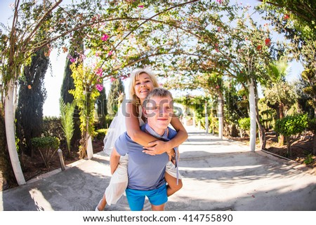 Happy couple. Man carrying woman on his back - stock photo
