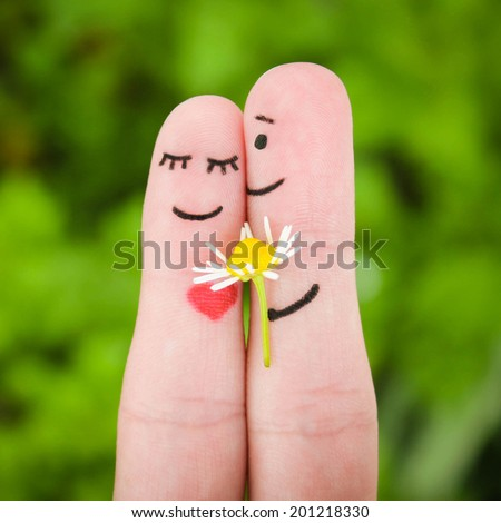 Happy couple. Man is giving flowers to a woman.  - stock photo