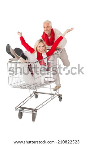 Happy couple messing about in shopping trolley on white background