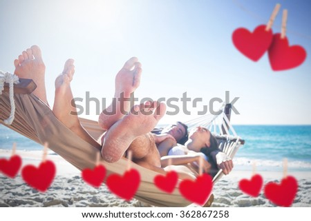 Happy couple napping together in the hammock against hearts hanging on a line - stock photo