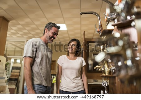 Happy couple of adults choosing bathroom faucets in plumbing store