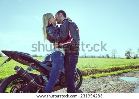 happy couple of bikers in love. they take a break after a ride in the countryside