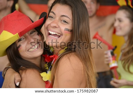 Happy couple of girlfriends sport soccer fans celebrating.