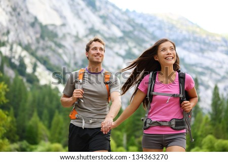 Happy couple of hikers hiking holding hands joyful, cheerful and fresh. Young active multiracial couple in outdoor activity hike in Yosemite National Park, California, USA. Asian woman, Caucasian man. - stock photo