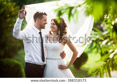 Happy couple of newlyweds posing under veil at sunset