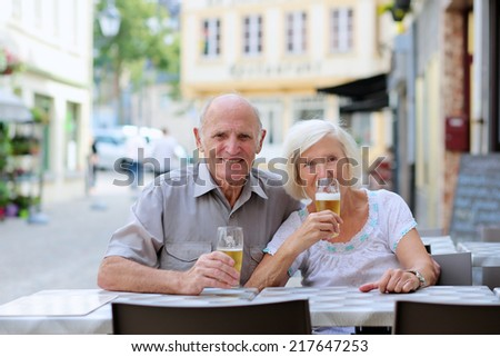 Happy couple of seniors, a man and his wife, are enjoying glass refreshing drink sitting at the open air terrace of cozy cafe in typical european city on a warm sunny day - active retirement concept