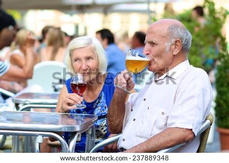 Happy couple of seniors, a man and his wife, are enjoying glass refreshing drink sitting at the open air terrace of cozy cafe in typical european city on a warm sunny day - active retirement concept - stock photo