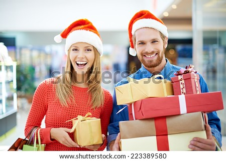 Happy couple of shoppers buying Christmas presents - stock photo