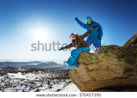 Happy couple of snowboarders sits and stands on a big rock on mountains valley backdrop. Sheregesh resort, Siberia, Russia  - stock photo