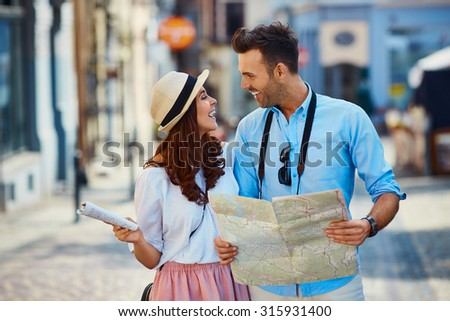 Happy couple of tourists in the city - stock photo