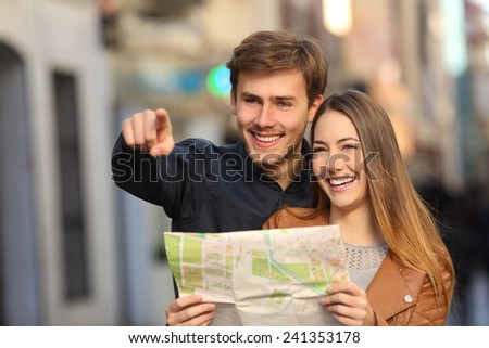 Happy couple of tourists on vacations searching a street in a map and pointing away - stock photo