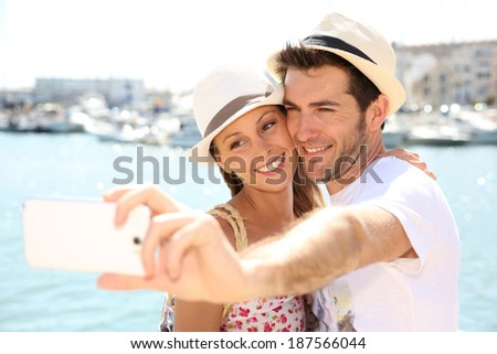 happy couple of tourists taking pictures with smartphone - stock photo