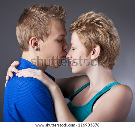 Happy couple of young people having fun together against black background - stock photo