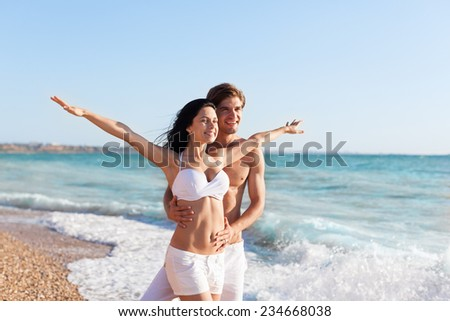 Happy couple on beach hold stretching hands, beautiful young happy man and woman love smile, concept summer ocean holiday travel