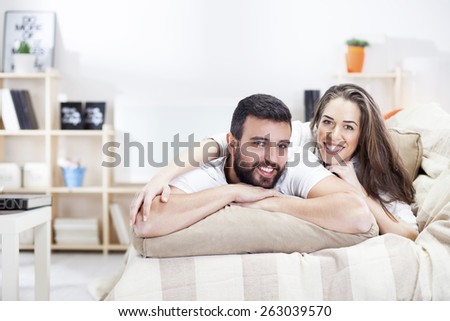 Happy couple on bed sofa in living room - stock photo