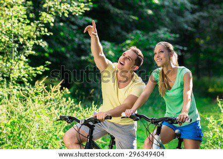 Happy couple on bicycles in summer - stock photo