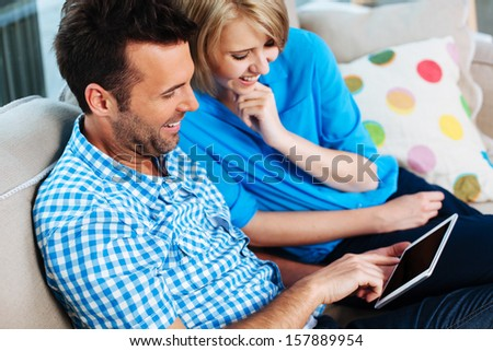 Happy couple on couch with digital tablet - stock photo