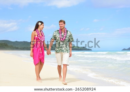 Happy couple on Hawaii vacation walking on beach with Hawaiian leis and Aloha clothing. Caucasian man wearing typical Hawaiian shirt and Asian woman girlfriend in pink sarong fabric sundress. - stock photo